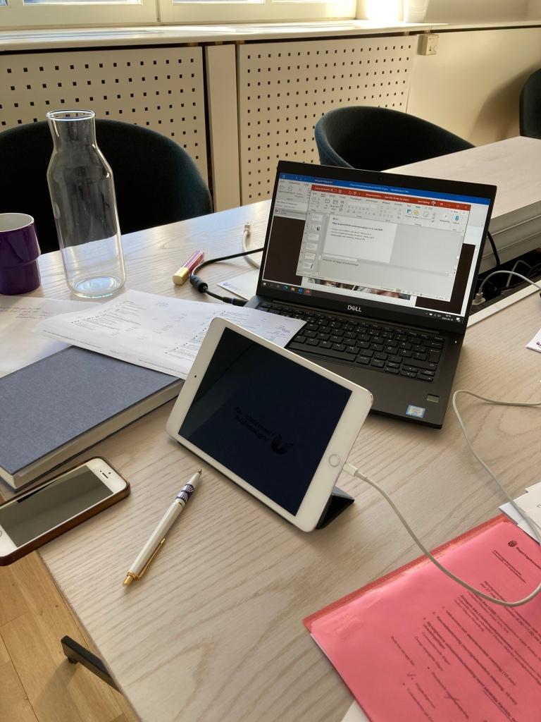 Mötesbord med dator, surfplatta, mobiltelefon, anteckningsblock, pappersmappar, kaffemugg och vattentillbringare